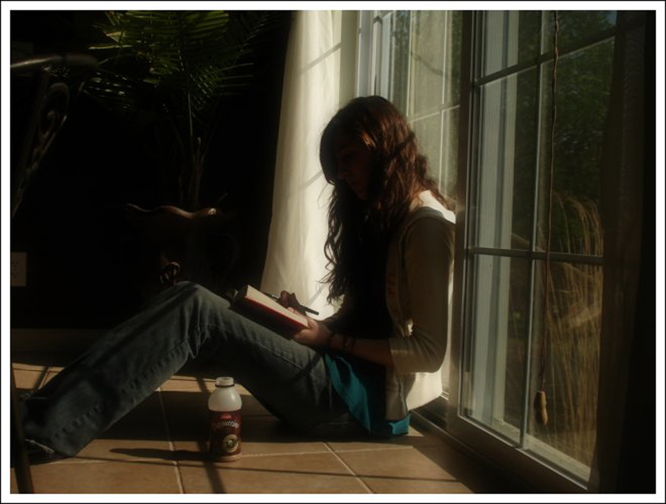 Young woman reading by window